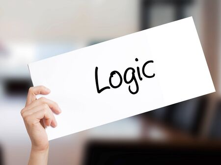 rationale: Logic Sign on white paper. Man Hand Holding Paper with text. Isolated on Office background.  technology, internet concept. Stock Photo