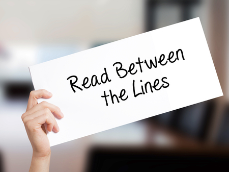 Read Between the Lines   Sign on white paper. Man Hand Holding Paper with text. Isolated on Office background.   Business concept. Stock Photo
