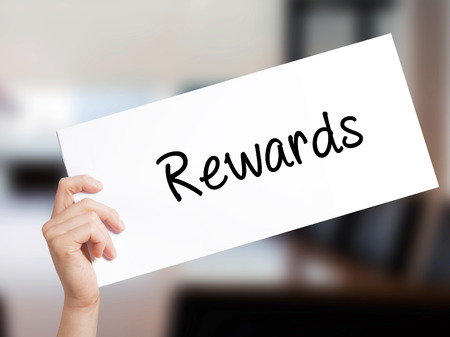 eminence: Rewards Sign on white paper. Man Hand Holding Paper with text. Isolated on Office background.   Business concept. Stock Photo