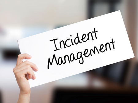iscp: Incident Management Sign on white paper. Man Hand Holding Paper with text. Isolated on Office background.   Business concept. Stock Photo