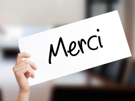 Merci  (Thank You In French) Sign on white paper. Man Hand Holding Paper with text. Isolated on Office background.  Business concept. Stock Photo