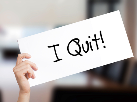 I Quit! Sign on white paper. Man Hand Holding Paper with text. Isolated on Office background.  Business concept. Stock Photo Stock Photo
