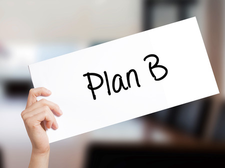 jargon: Plan B Sign on white paper. Man Hand Holding Paper with text. Isolated on Office background.   Business concept. Stock Photo
