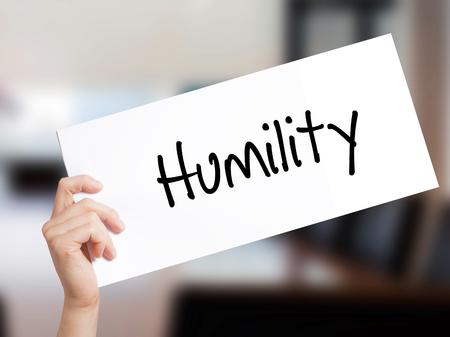 白い紙の上の謙虚さの標識です。男の手を保持している紙本文。事務所のバック グラウンド上に分離。 ビジネス コンセプトです。ストック フォト