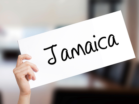 rastafari: Jamaica  Sign on white paper. Man Hand Holding Paper with text. Isolated on Office background.   Business concept. Stock Photo