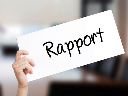 Rapport Sign on white paper. Man Hand Holding Paper with text. Isolated on Office background.   Business concept. Stock Photo