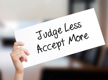 favoritism: Judge Less Accept More Sign on white paper. Man Hand Holding Paper with text. Isolated on Office background.  Business concept. Stock Photo