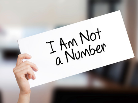 I Am Not a Number Sign on white paper. Man Hand Holding Paper with text. Isolated on Office background.  Business concept. Stock Photo