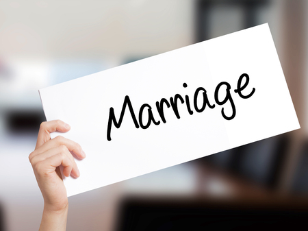 rupture: Marriage Sign on white paper. Man Hand Holding Paper with text. Isolated on Office background.   Business concept. Stock Photo