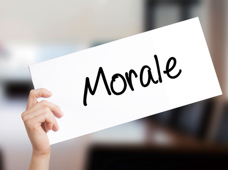 normative: Morale Sign on white paper. Man Hand Holding Paper with text. Isolated on Office background.   Business concept. Stock Photo