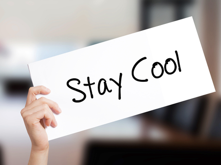 Stay Cool   Sign on white paper. Man Hand Holding Paper with text. Isolated on Office background.  Business concept. Stock Photo