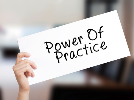 Power Of Practice Sign on white paper. Man Hand Holding Paper with text. Isolated on Office background.  Business concept. Stock Photo
