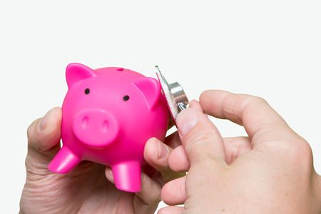 Man hand stethoscope pink piggy bank Isolated on white background. Health care cost. Financial state condition self assessment concept. Financial system checkup, savings for medical insurance costs