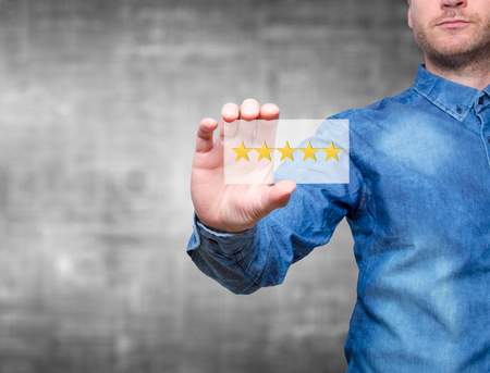 Man holding five star rating. Five stars service. Grey background - Stock Image Stok Fotoğraf