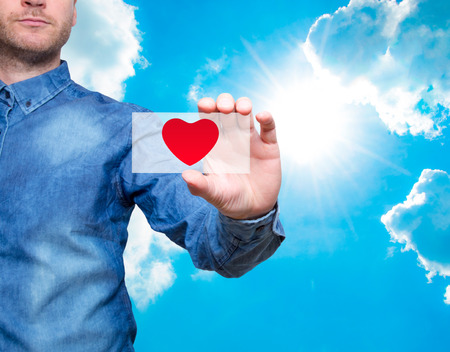 Young man holding heart background , service mind concept Sky background