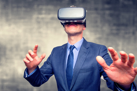 Businessman in a suit wearing Virtual Reality Goggles isolated on grey background