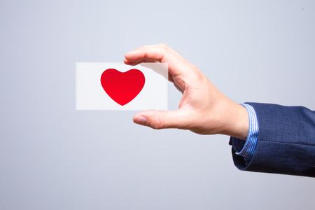 oriented: Businessman holding a red heart in his hand - crm - service mind