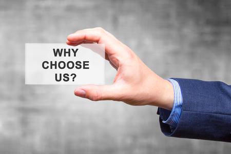 Zakenman hand bedrijf Waarom kiezen voor ons? teken geïsoleerd op een grijze achtergrond. Bedrijfsconcept. Stock foto Stockfoto