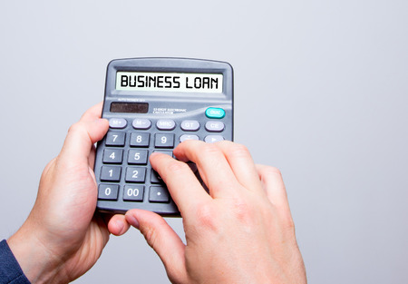 lend: Businessman hands holding Calculator with Business Loan sign text message isolated on white Stock Photo