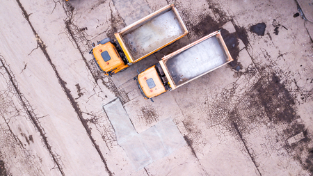 Aerial view of two orange trucks. in front of warehouse.