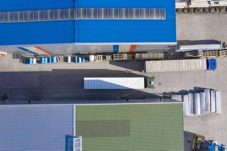Aerial view, logistic warehouse, trucks ride near warehouse ramp. Stock Photo
