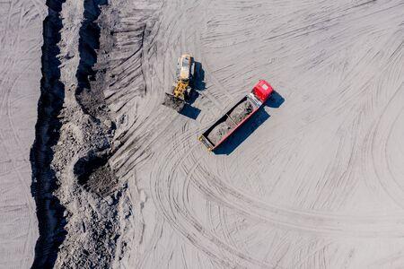 Luftaufnahme des Sandsteinbruchs mit Lastwagen und Bulldozern. Schwerer Bulldozer lädt Sand, Standard-Bild