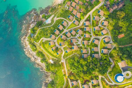 Aerial panorama of tropical resort territory and beach, beautiful Andaman sea at west coast of Phuket Island. Kata Noi beach from above, some buildings and green hills, calm sea surface to horizon