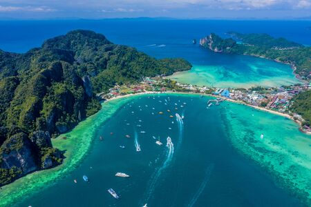 Blue clear water with boats. Green tropical island Phi Phi, palm trees grow. Shooting from a drone from the air. Beautiful seascape. Turquoise color of the water, you can see the bottom and corals.