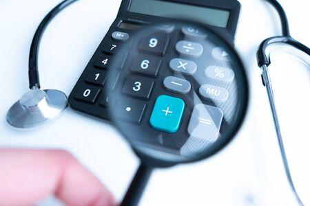 Konzept der Krankheitskosten oder Krankenversicherung für Blog-Titel und Header. Stethoskop, weißer Taschenrechner und Lupe auf hölzernem Hintergrund. Standard-Bild