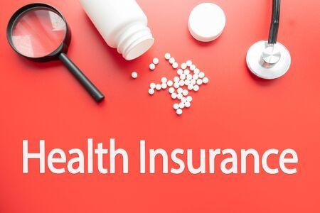 Health insurance word with stethoscope - health concept. Medical conceptual. Pharmaceutical medicine pills, tablets and capsules and bottle on red background. Banco de Imagens