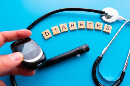 Diabetes wooden text. Flat lay composition with glucose meter and stethoscope on light blue background. Space for text
