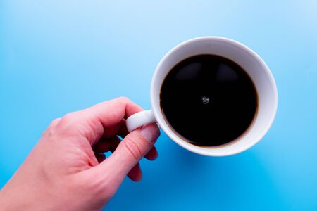 Cups of black tea in the hands of men on a blue background. with copy space. top view 版權商用圖片