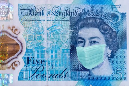 Queen Elizabeth II 5 pounds With Worried and Concerned Expression Wearing Medical White  Face Mask On five pounds Bill Фото со стока