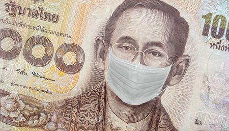Close up of Thai banknote, Thai bath with the image of King Bhumibol Adulyadej Worried and Concerned Expression Wearing Medical White  Face Mask . Thai on 1000 bath Banknote from Thailand.
