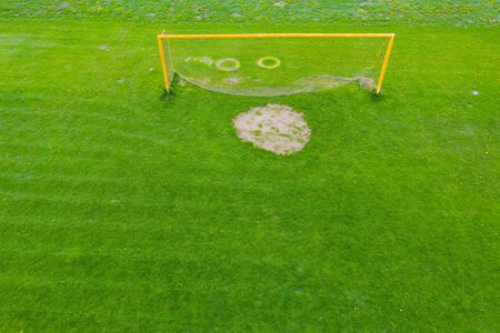 Football net on the background of a green football field. Aerial view of football gate