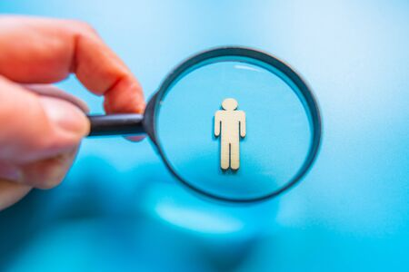 Employee search HR concept - magnifier with abstract employee on a blue background. Close up.