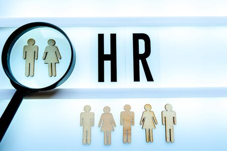 Employee search HR concept - magnifier with abstract employee on a white background. Close up.