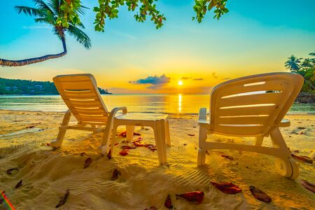 Beautiful tropical sunset scenery, two sun beds, loungers, umbrella under palm tree. White sand, sea view with horizon, colorful twilight sky, calmness and relaxation. Inspirational beach resort hotel Banque d'images
