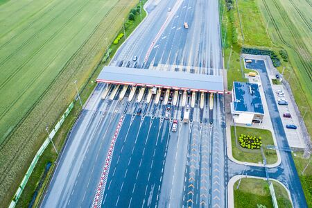 Car traffic transportation on multiple lanes highway road and toll collection gate, drone aerial top view. Commuter transport, city life concept.A2 Poland Lodz