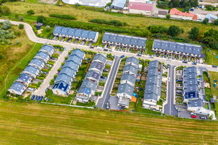 Aerial view of residential houses and driveways neighborhood. Tightly packed homes, surrounds with green tree flyover Europe. Suburban housing community development