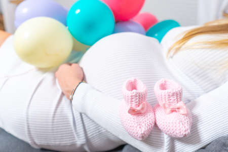 Beautiful pregnant woman is smoothing her tummy and smiling during baby shower