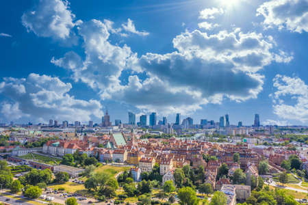 Aerial panorama of Warsaw, Poland over the Vistula river and City center in a distance. Sky Clouds and sun
