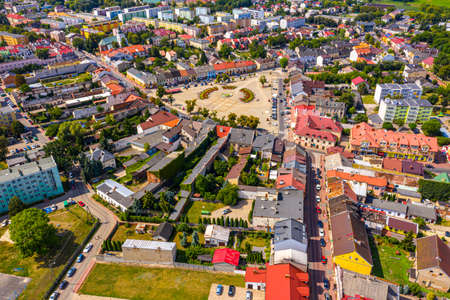 Top aerial panoramic view of Lowicz old town historical city center with Rynek Market Square, Old Town Hall, New City Hall, colorful buildings with multicolored facade and tiled roofs, Poland