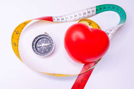 Top view red heart shape and white measurement tape on white background. For heart check up or checking size concept. Healthy heart Standard-Bild