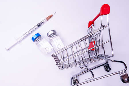 Mini shopping trolley with syringes, injections, vaccines and blood tubes on white background. Vaccination concept
