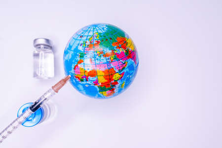 Medical hand injecting a vaccine into planet Earth. Standard-Bild