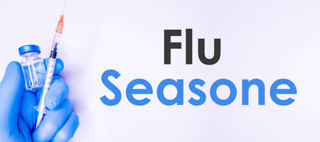 Text Flu Season on a white background with syringes and ampule. Medical concept photo