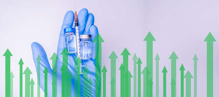 Hands of a researcher in medical gloves takes shot from Vaccine vial by needle syringe with stock index chart rising up in the background.