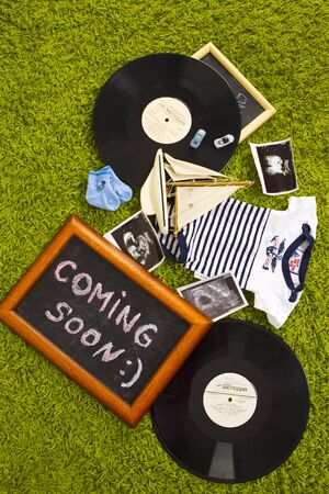 anticipation: composition of the vinyl, toy cars and wooden plates in anticipation of the child Stock Photo