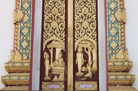 Thai art carving and painting on door of temple photo